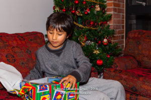 Bogota, Colombia - Child excitedly opens Christmas present