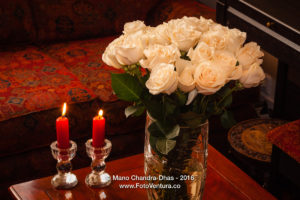 Cream coloured roses and red unlit candles