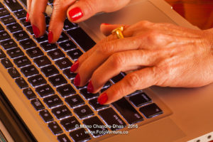 Older Latin lady's hands on laptop computer keyboard