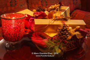 Christmas - gifts in gold boxes; ribbons, pine cone and candle.