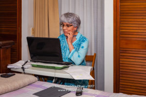 Senior Hispanic Lady With Silver Hair, Working From Home On Her Computer