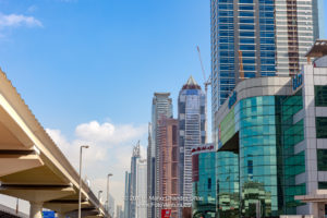 Dubai, United Arab Emirates - A Low Angle View Of Buildings On Sheikh Zayed Road; To The Left Are The Elevated Metro Tracks