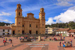 Chiquinquirá, Boyacá Department, Colombia - Local Colombians On The Main Town Square On A Sunday Afternoon; Background: Basilica Of Our Lady Of The Rosary