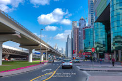 Dubai, United Arab Emirates - Elevated Railway Track To The Left And Modern Skyscrapers To The Right, Where Once Was Only Sand And A Desert Road; Road Markings In Foreground.