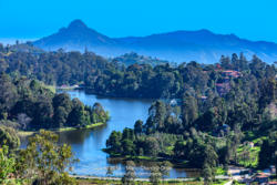 Kodaikanal, South India - Looking Down At Kodaikanal Lake From A Higher Elevation In The Colonial Town In The State Of Tamil Nadu; In The Far Background Is The Peak Known Locally As Perumal Malai