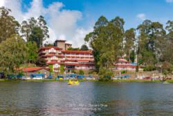 Kodaikanal, South India - Looking From Kodaikanal Lake Towards The Carlton Hotel, In The Colonial Town In The State Of Tamil Nadu; Several Tourists' Cars Are Parked By The Lakeside.