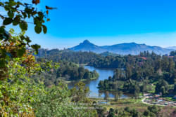 Kodaikanal, South India - Looking Down At Kodaikanal Lake From A Higher Elevation In The Colonial Town In The State Of Tamil Nadu; In The Far Background Is The Peak Known Locally As Perumal Malai. No people.