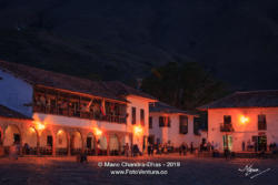 Colombia, South America - Tourists And Some Local Residents At Twilight Time, On The Eastern Corner Of The Main Square In The Historic 16th Century Town of Villa de Leyva In The Boyacá Department