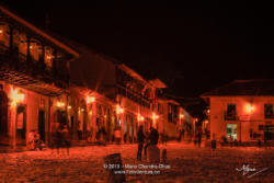 Colombia, South America - Tourists And Some Local Residents On The Eastern Corner Of The Plaza Mayor In The Historic 16th Century Town of Villa de Leyva In The Boyacá Department, Just After Sunset; Night Shot Lit By Street Lights